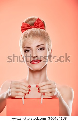 Beauty fashion portrait loving woman smiling with shopping bag. Confidence sensual attractive pretty nude blonde sexy girl, Pinup hairstyle, red bow. Unusual playful. Romantic on pink, sale, discount - stock photo