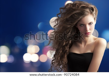 beauty fashion portrait of a very young cute brunette with long curly hair with hairstyle flying in the wind on bokeh background - stock photo