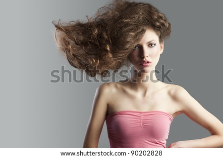 beauty fashion portrait of beautiful young brunette with curly hair flying and creative hairstyle. she looks in to the lens, has hair raised on the right and left hands on left hip. - stock photo