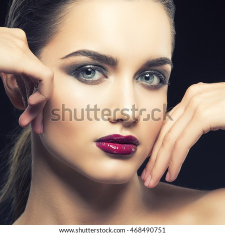 Beauty fashion portrait of caucasian brunette woman wet red lipstick and arms touching face. Isolated on black background. Toned