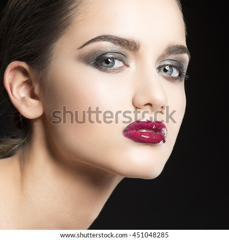 Beauty fashion portrait of caucasian brunette woman wet wet red lipstick and arms touching face. Isolated on black background.  - stock photo