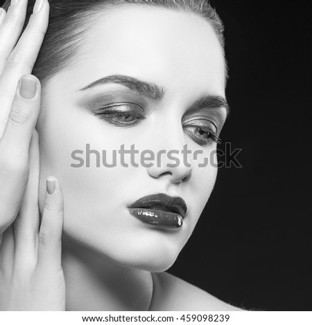 Beauty fashion portrait of caucasian brunette woman with wet red lipstick and arms touching face. Isolated on black background. Black and white