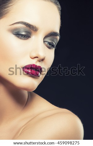 Beauty fashion portrait of caucasian brunette woman with wet red lipstick. Isolated on black background. Toned
