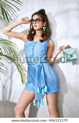 Beauty fashion style model woman holidays vocation girl wear sexy clothes accessory handbag brunette hair bracelet jewelry skinny body tan travel collection palm shadow vogue pose makeup pretty face - stock photo