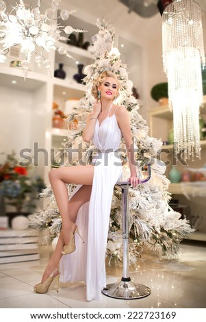 Beauty fashion woman at Christmas background new year tree. Vogue style sexy girl.  Gorgeous girl in luxury fur at Xmas party. Luxury life concept. Retro style girl. makeup   fashion jewelry model - stock photo