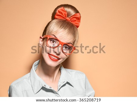Beauty fashion woman in stylish glasses thinking, idea. Attractive pretty funny blonde hipster girl smiling.Confidence, success, Pinup hairstyle bow makeup. Unusual playful, expression.Vintage, yellow