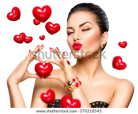Beauty Fashion Woman showing red heart in her hand. Love concept, Valentine's Day. Beautiful model girl winking and kissing. Isolated on a white background - stock photo