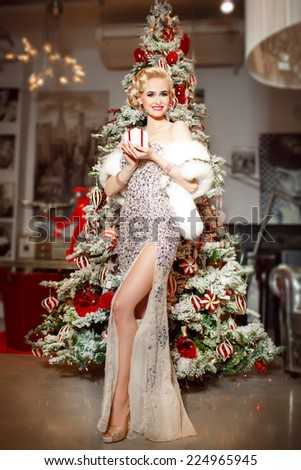 Beauty fashion woman with Christmas gift box, new year tree background. Vogue style sexy girl. Gorgeous girl in luxury fur at Xmas party. Luxury life concept. Retro style girl makeup and jewelry model - stock photo
