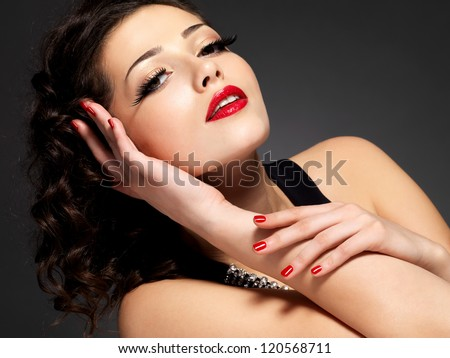 Beauty fashion woman with red nails, lips and golden eye makeup  - on black background - stock photo