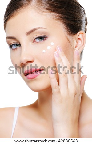 Beauty female applying cosmetic cream on skin around eyes - isolated on white - stock photo