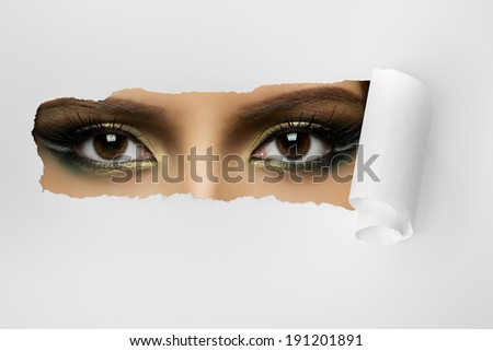 beauty female eye on scrap of paper, on white sheet, horizontal photo