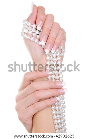 Beauty female fingernails with french manicure and  perl - over white background - stock photo