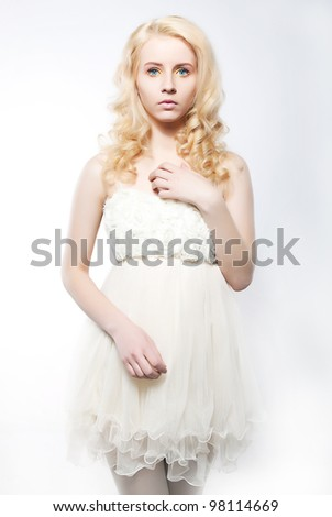Beauty fresh blonde woman with beautiful blue eyes in white bridal dress posing