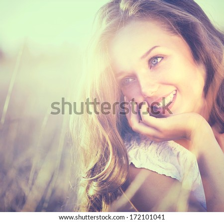 Beauty Fresh Romantic Girl Outdoors. Nature. Spring Sunset. Beautiful Model young Woman with long hair on a Field Smiling. Teenage Girl Lying on the Field in Sun Light. Glow Sun, Sunshine. Backlit.