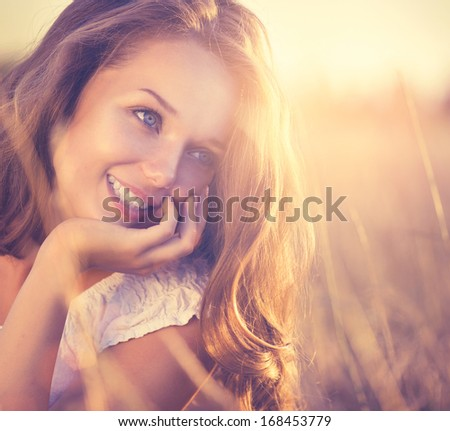 Beauty Fresh Romantic Girl Outdoors. Nature. Sunset. Beautiful Model young Woman with long hair on a Field Smiling. Cute Teenage Girl Lying on the Field in Sun Light. Glow Sun, Sunshine. Backlit.