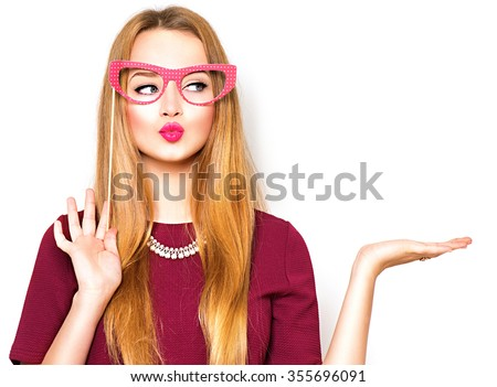 Beauty funny teenage girl with paper glasses on stick showing empty copy space on the open hand palm for text, white background. Happy girl presenting point. Proposing product. Advertisement gesture - stock photo