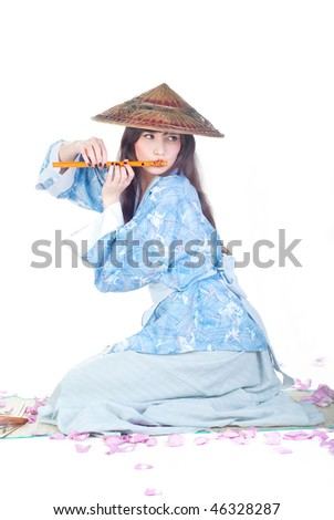 beauty geisha in blue kimono sit on mat and play the flute