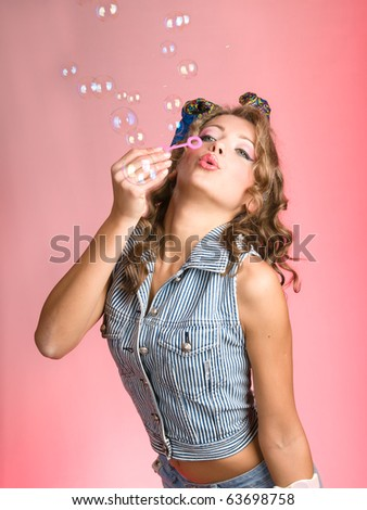 Beauty girl blows bubbles against a pink background - stock photo