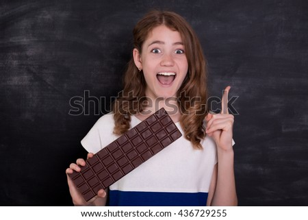 Beauty girl eating chocolate. Beautiful Surprised young woman takes chocolate sweets. Funny girl on chalkboard background - stock photo