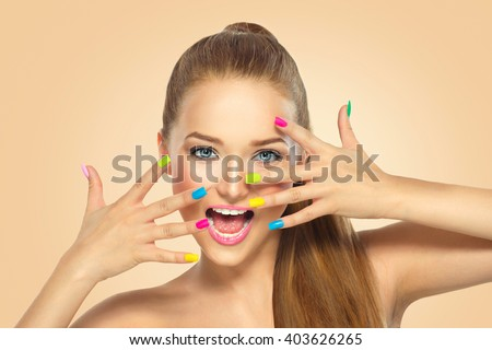 Beauty Girl Face with Colorful Nail polish. Colourful Studio Shot of young Woman. Vivid Colors. Colourful Manicure and fashion Makeup. Rainbow Colors. Beautiful lady touching her face - stock photo