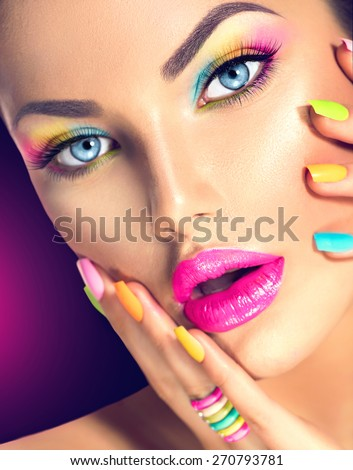 Beauty Girl face with Vivid Makeup and colorful Nail polish. Colourful nails. Fashion Woman portrait close up. Bright Colors. Blue eyes, long eyelashes, vivid eyeshadows Rainbow make up - stock photo