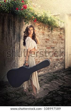 Beauty girl holding guitar outside - stock photo