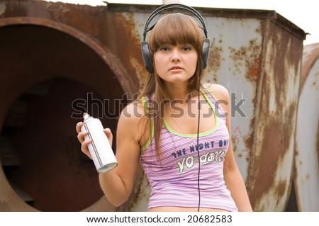 beauty girl in headphones painting near constructions - stock photo