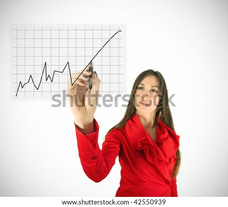 Beauty girl in red writing rising diagram. Focus is on hand with pen.