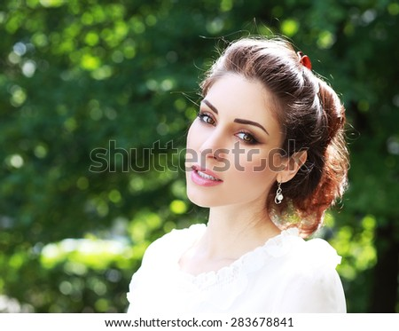 Beauty Girl in the Meadow. Beautiful Young Woman Outdoors. Enjoy Nature. Healthy Smiling Girl lying on Green Grass with wild Flowers. Laughing And Happy - stock photo