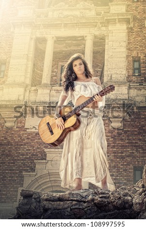 Beauty girl in white playing guitar outside