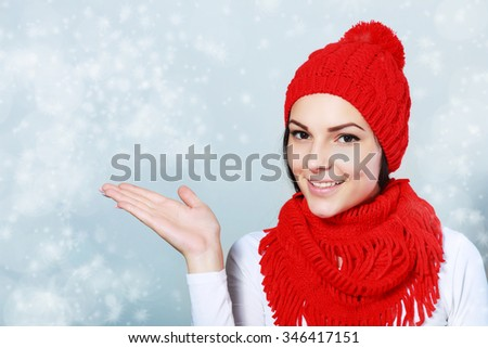 beauty girl on the winter background show palm pointing to copyspace - stock photo