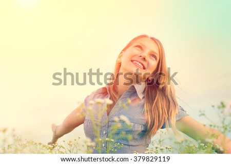 Beauty Girl Outdoors enjoying nature. Beautiful Teenage Model girl having fun on spring Field with blooming flowers, raising hands in Sun Light. Sunrise. Glow Sun. Free Happy Woman, allergy free - stock photo