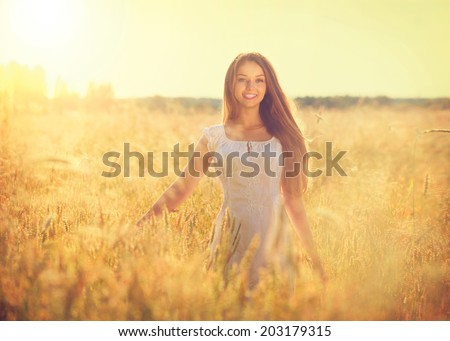 Beauty Girl Outdoors enjoying nature. Beautiful Teenage Model girl in white dress running on the Field, Sun Light. Glow Sun. Free Happy Woman. Toned in warm colors. Autumn - stock photo