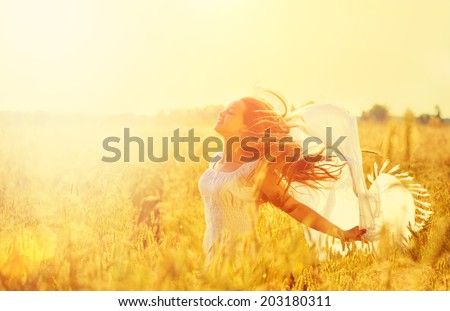 Beauty Girl Outdoors enjoying nature. Beautiful Teenage Model girl in white dress running on the Spring Field, Sun Light. Glow Sun. Free Happy Woman. Toned in warm colors - stock photo