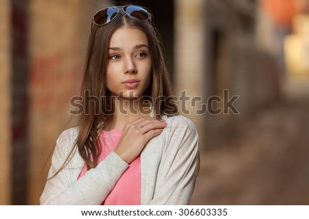 Beauty Girl Outdoors enjoying nature. Beautiful Teenage Model girl with long healthy blowing hair running on the Spring Field, Sun Light. Glow Sun. Free Happy Woman. Toned in warm colors - stock photo