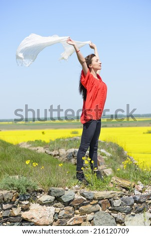 Beauty Girl Outdoors enjoying nature. Field. Freedom and lifestyle concept. Series. Happy young woman holding white scarf with opened arms expressing freedom, outdoor shot against blue sky. - stock photo