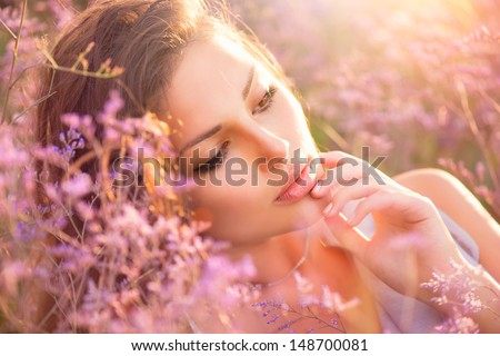 Beauty Girl Portrait. Sensual Woman Lying on a Meadow with Violet Flowers. Beautiful Woman Enjoing Nature - stock photo
