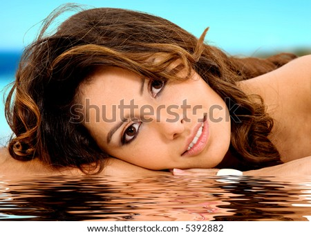 beauty girl portrait with a water reflection and a beach in the background