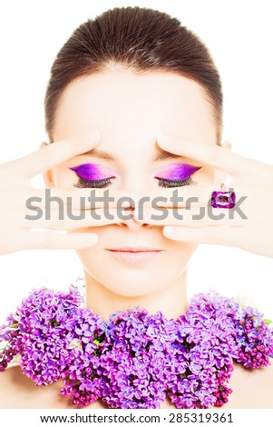Beauty Girl Portrait with Colorful Makeup, Nail Polish, ring Accessories and Purple Flowers. Colourful eye shadows Make-up - stock photo