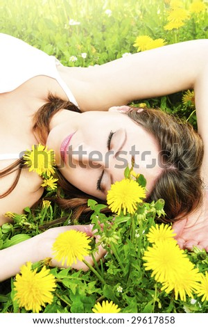 beauty girl relaxing in the grass and flowers - stock photo