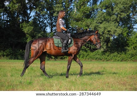 Beauty girl rides horseback in evening park - stock photo
