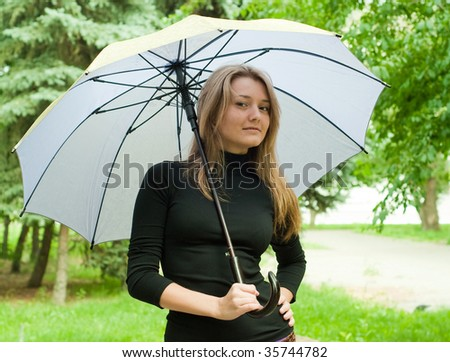 beauty girl stay with umbrella in the park on trees background - stock photo