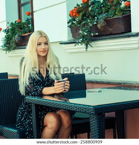 Beauty Girl With Cup of Coffee. Beautiful young woman with a cup of tea at a cafe - stock photo
