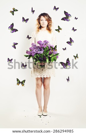 Beauty Girl with Flowers and  Butterfly. Beautiful Model woman with Blooming flowers on her hand. Nature Hairstyle. Summer Fashion Creative Background. Vogue Style Portrait - stock photo