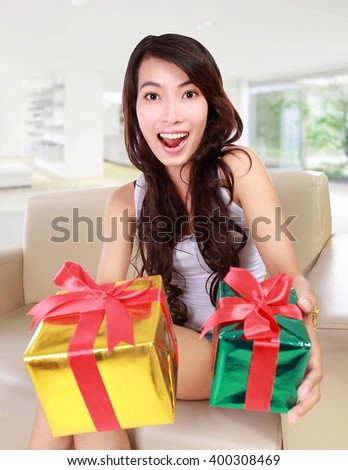 beauty girl with gift box sitting on sofa at home