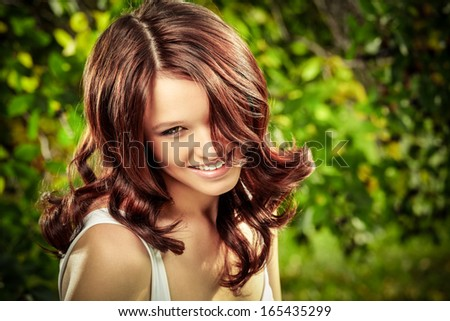 Beauty girl with magnificent curly ringlets against a summer garden - stock photo