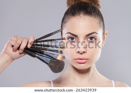 Beauty girl with makeup brushes. Perfect smooth skin.Applying makeup.Beautiful young woman holding different make up brushes - stock photo