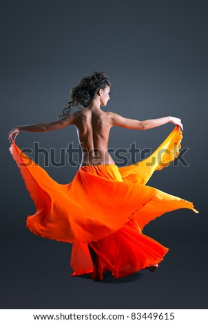 Beauty girl with naked spine dance in orange cloth - stock photo