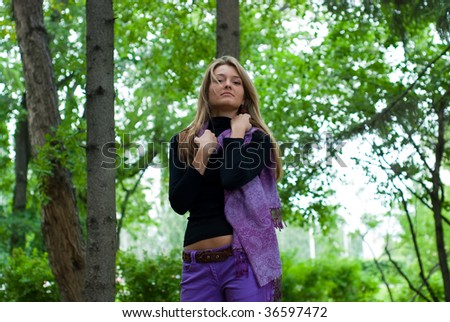 beauty girl with violet scarf in the park on trees background - stock photo