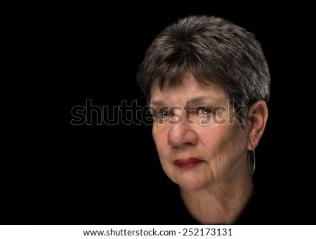 Beauty glamor portrait of senior elderly older woman with short brown hair and bright soft skin with serious melancholy sad depressed disappointed judgmental expression isolated on black background